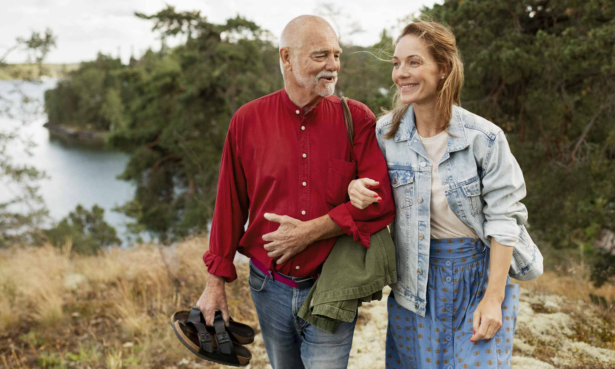Man and woman arm in arm walking up from a lake